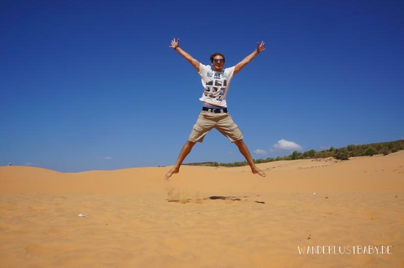 Mann springt bei Sanddünen