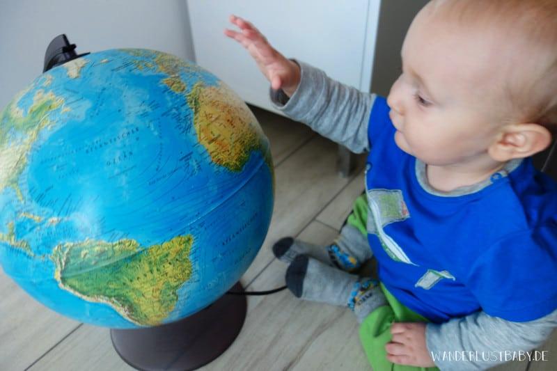 Baby spielt mit Globus