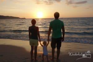 Familie am Strand zum Sonnenuntergang