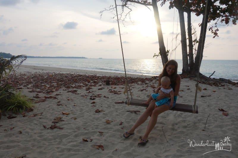Mutter schaukelt mit Kind am Strand
