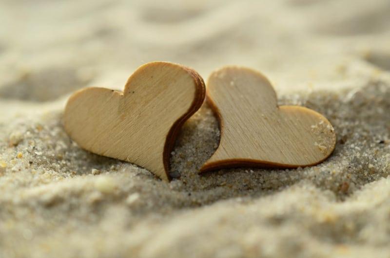 Zwei Holzherzen im Strand