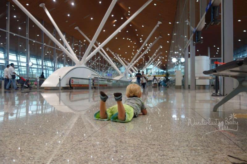 Baby auf dem Boden liegend im Flughafen