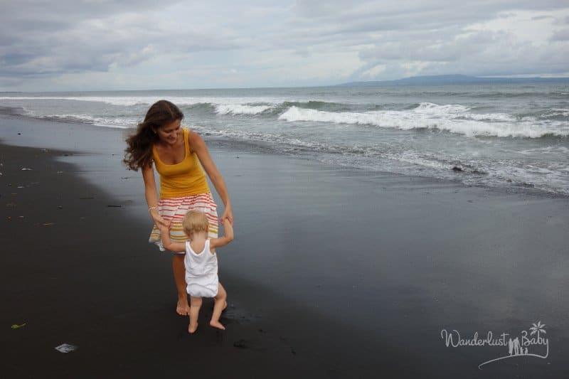 Frau mit Kind am schwarzen Strand