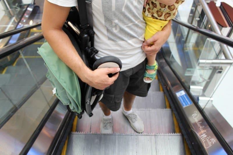 zusammengeklappter Buggy auf Rolltreppe