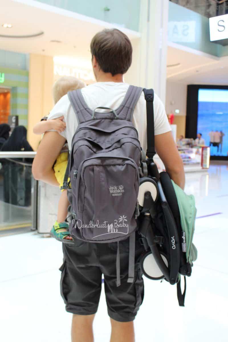 Mann mit Kind und Reisebuggy