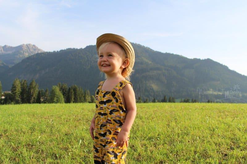 Kind mit Sonnenhut auf der Wiese