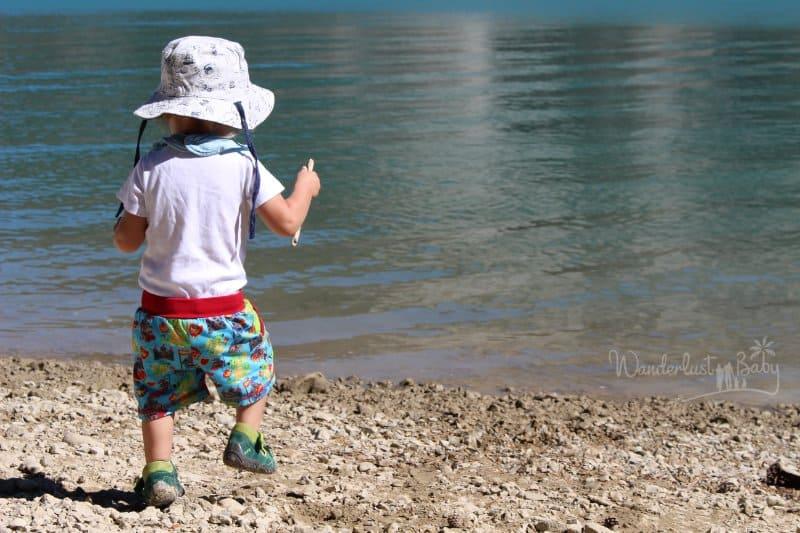 Kind mit Hut am Wasser